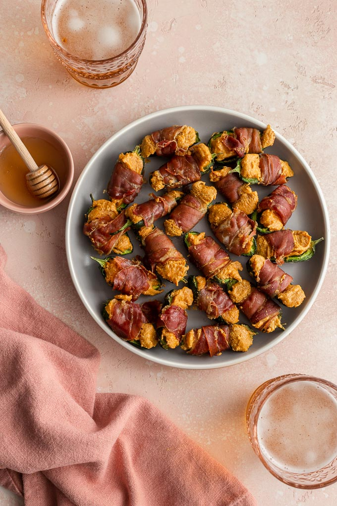 Dairy-free jalapeño poppers arranged on a grey plate next to some honey and glasses of beer.