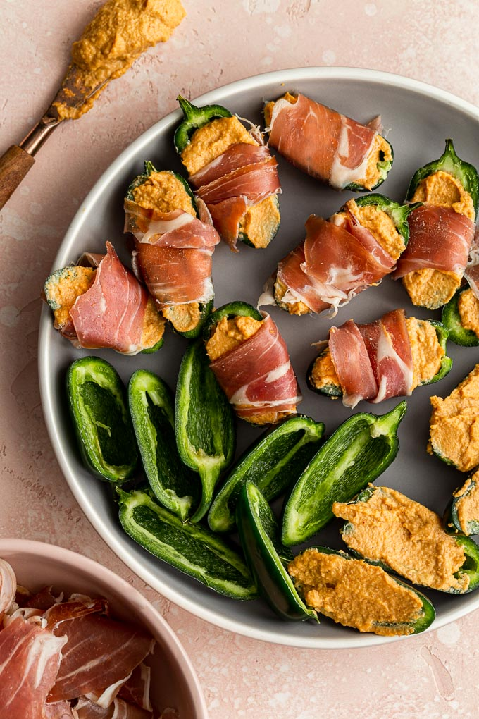 Jalapeño halves arranged on a plate, being stuffed with cashew cheese and wrapped in prosciutto.