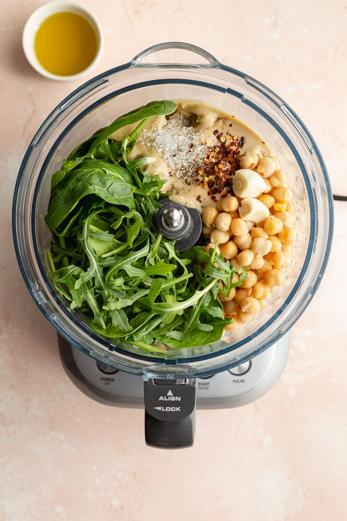Overhead view of ingredients to make green hummus in a food processor bowl.