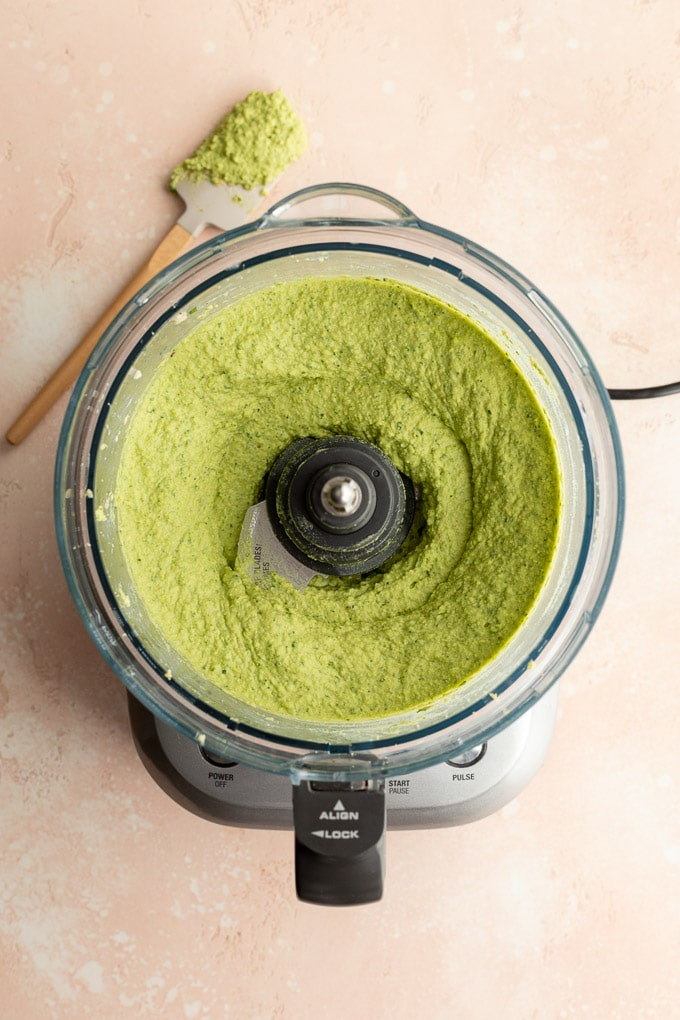 Green hummus whipped up in a food processor bowl.