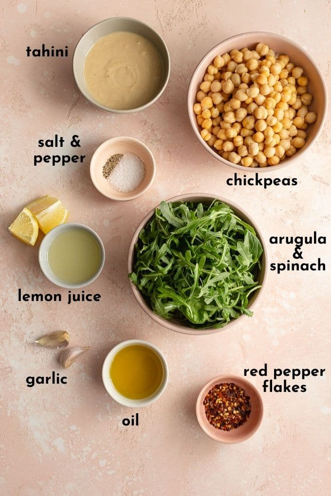 Ingredients to make arugula hummus arranged individually and labelled.