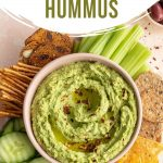 Pinterest image of green hummus in a bowl with veggies and chips on the side.