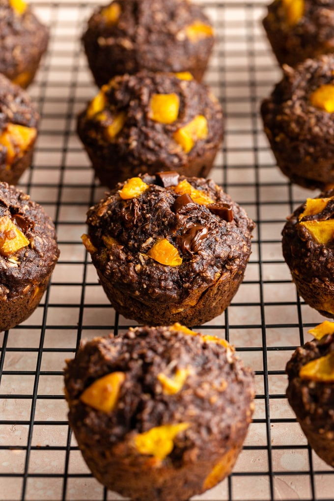 Side view of double chocolate mango muffins on a wire rack.