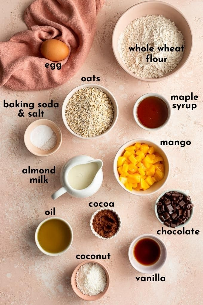 Ingredients to make mango coconut muffins arranged individually and labelled.
