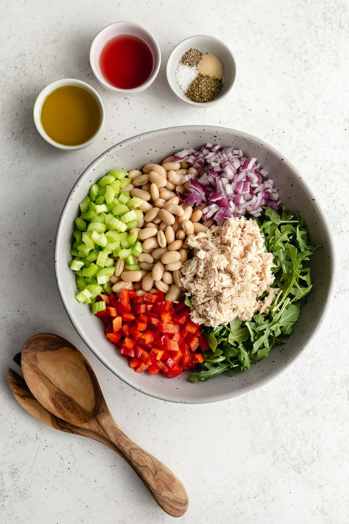 Ingredients to make tuna white bean salad assembled in a large bowl with dressing ingredients on the side.