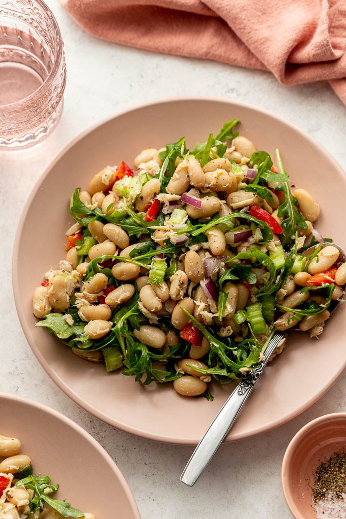 Up close and overhead view of bean salad on a pink plate with a fork.