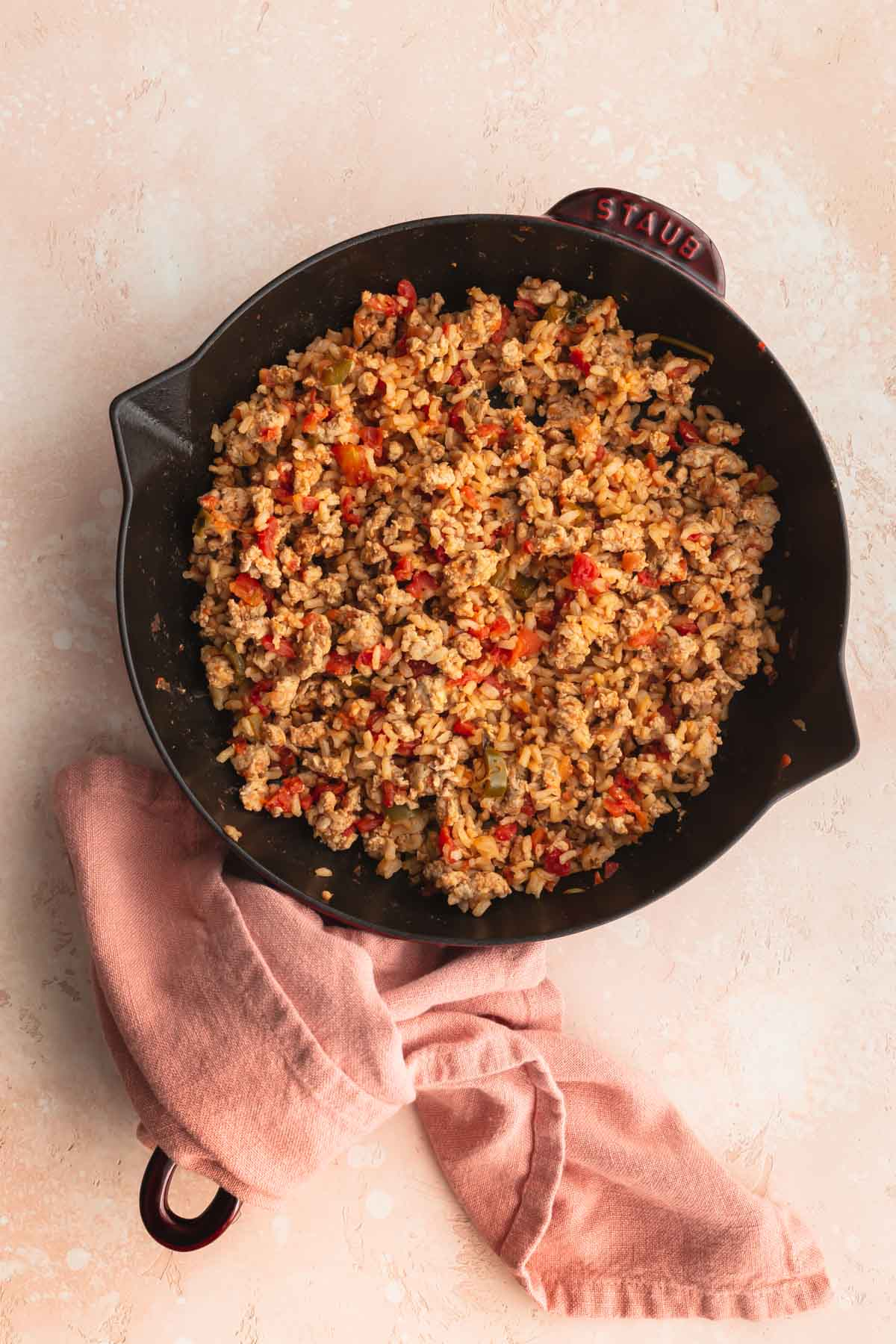 Turkey mixture for the stuffed peppers in a cast iron skillet.