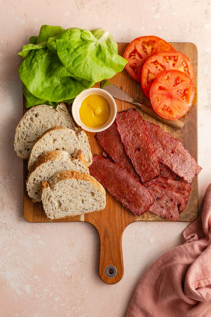 Ingredients to make a turkey bacon, lettuce and tomato sandwich arranged on a wooden board.