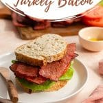 Pinterest image of a turkey bacon, lettuce and tomato sandwich on a white plate.