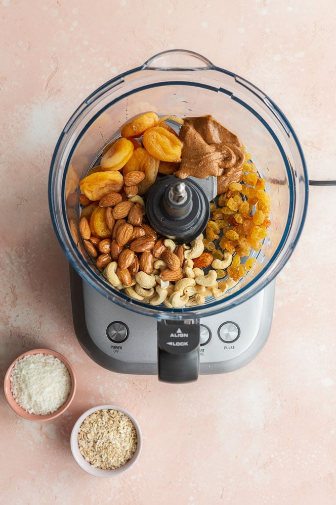 Ingredients to make apricot bliss balls in a food processor bowl.