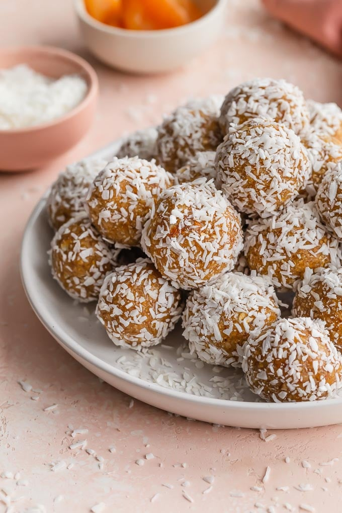 Close up of apricot balls covered in coconut and piled on a white plate.