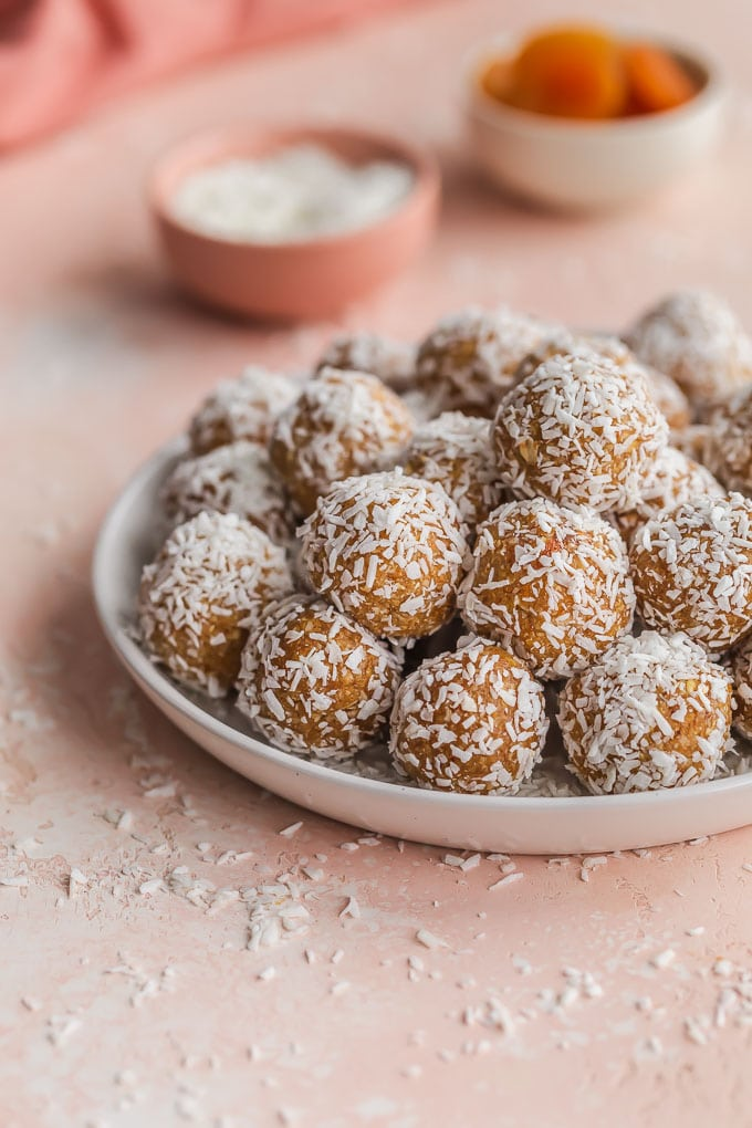 Healthy apricot balls rolled in coconut and arranged on a white plate on a pink surface.