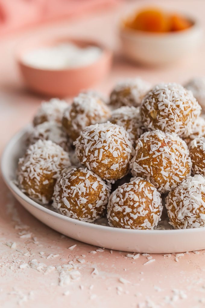Side view of coconut apricot balls piled on a white plate.