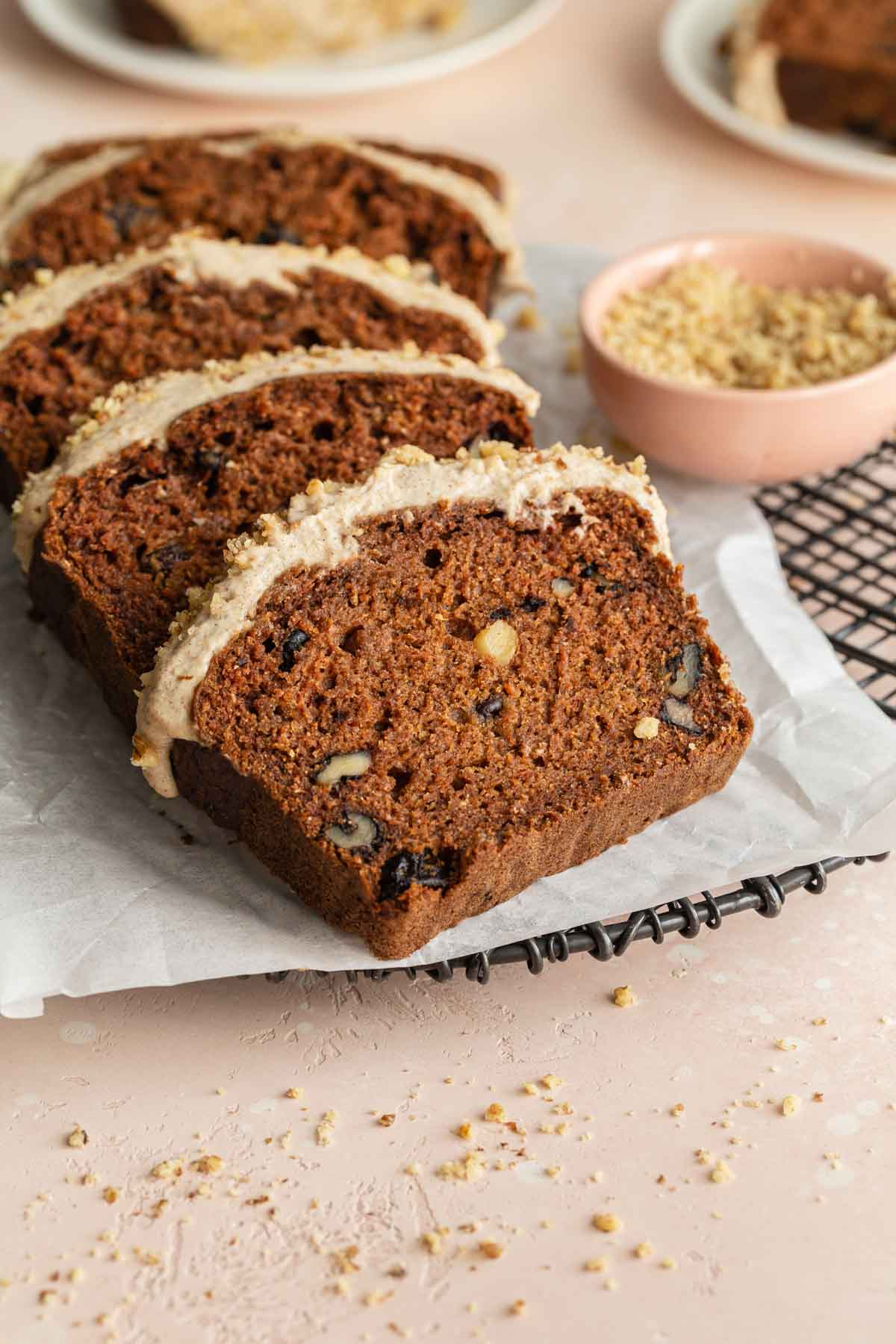 Slices of carrot cake loaf arranged on a sheet of parchment paper on a cooling rack.