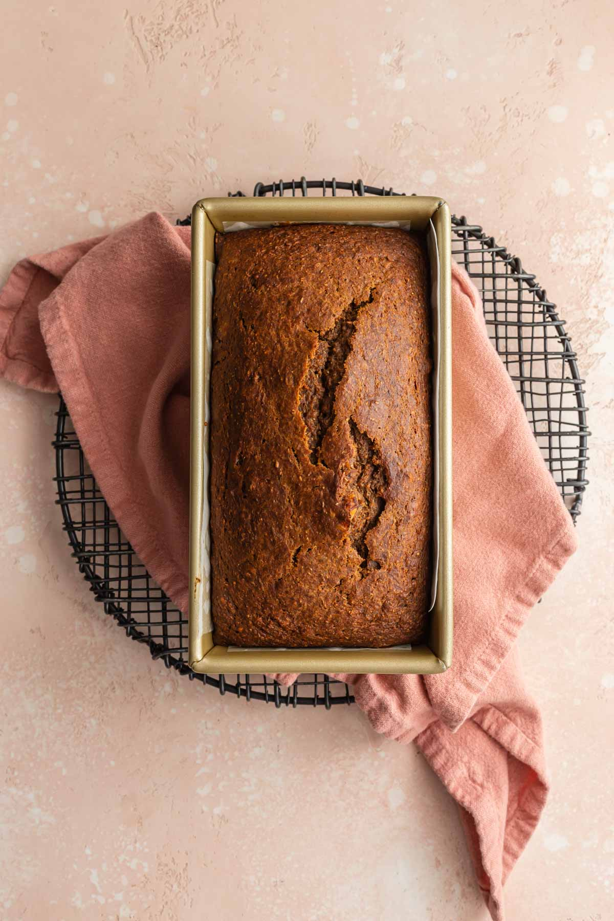 Overhead view of carrot cake bread baked up in a loaf pan and cooling on a wire rack.