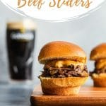 Pinterest image of Guinness beef sliders arranged on a cutting board with a glass of Guinness in background.