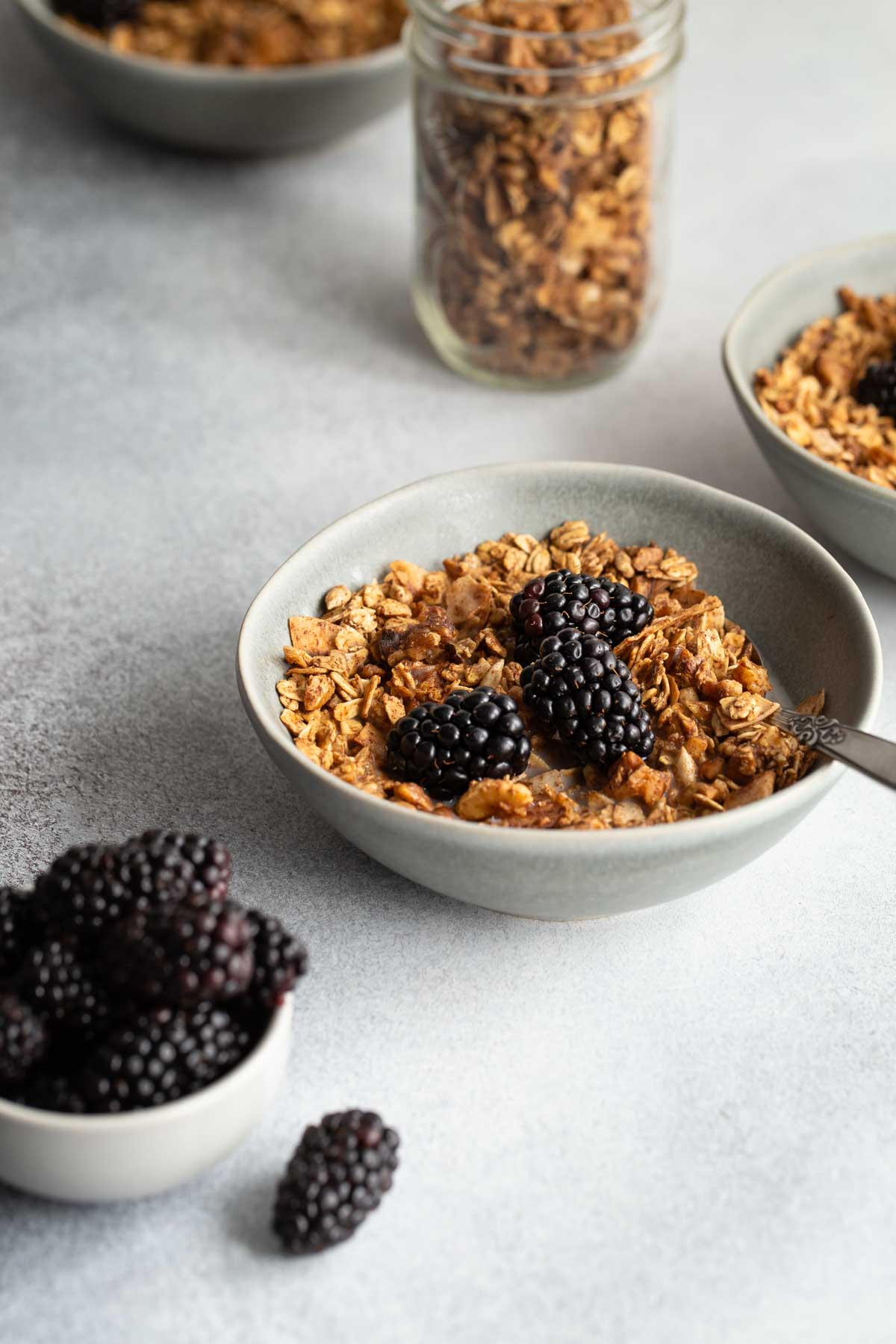 Side view of a bowl of maple syrup granola topped with blackberries, with granola in the background.