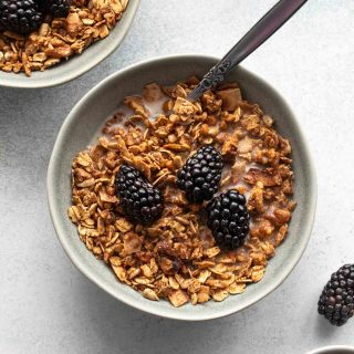 Overhead view of maple granola in a grey bowl and topped with milk and blackberries.
