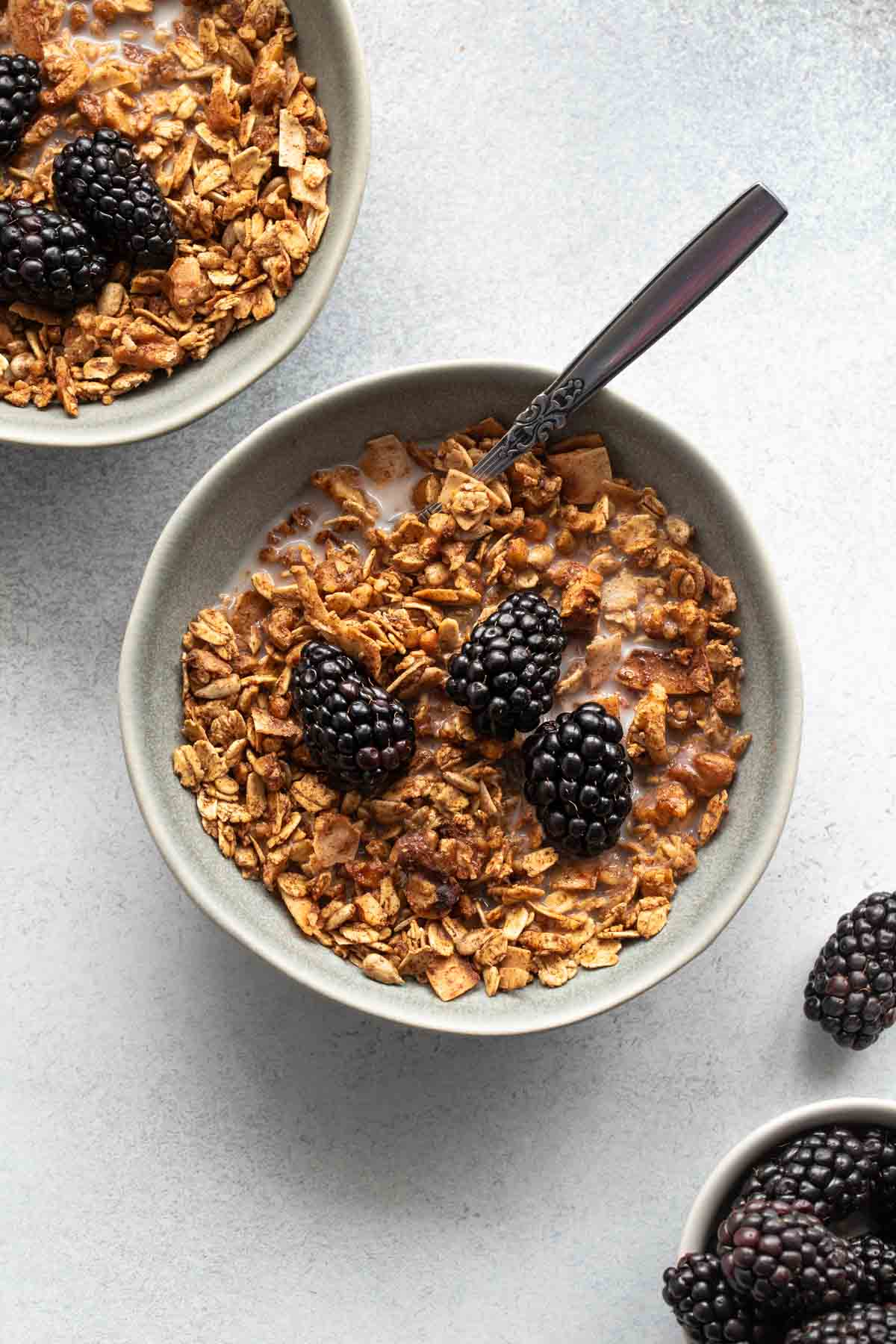 Overhead view of maple granola in a grey bowl and topped with almond milk and blackberries, with another bowl of granola off to the side.