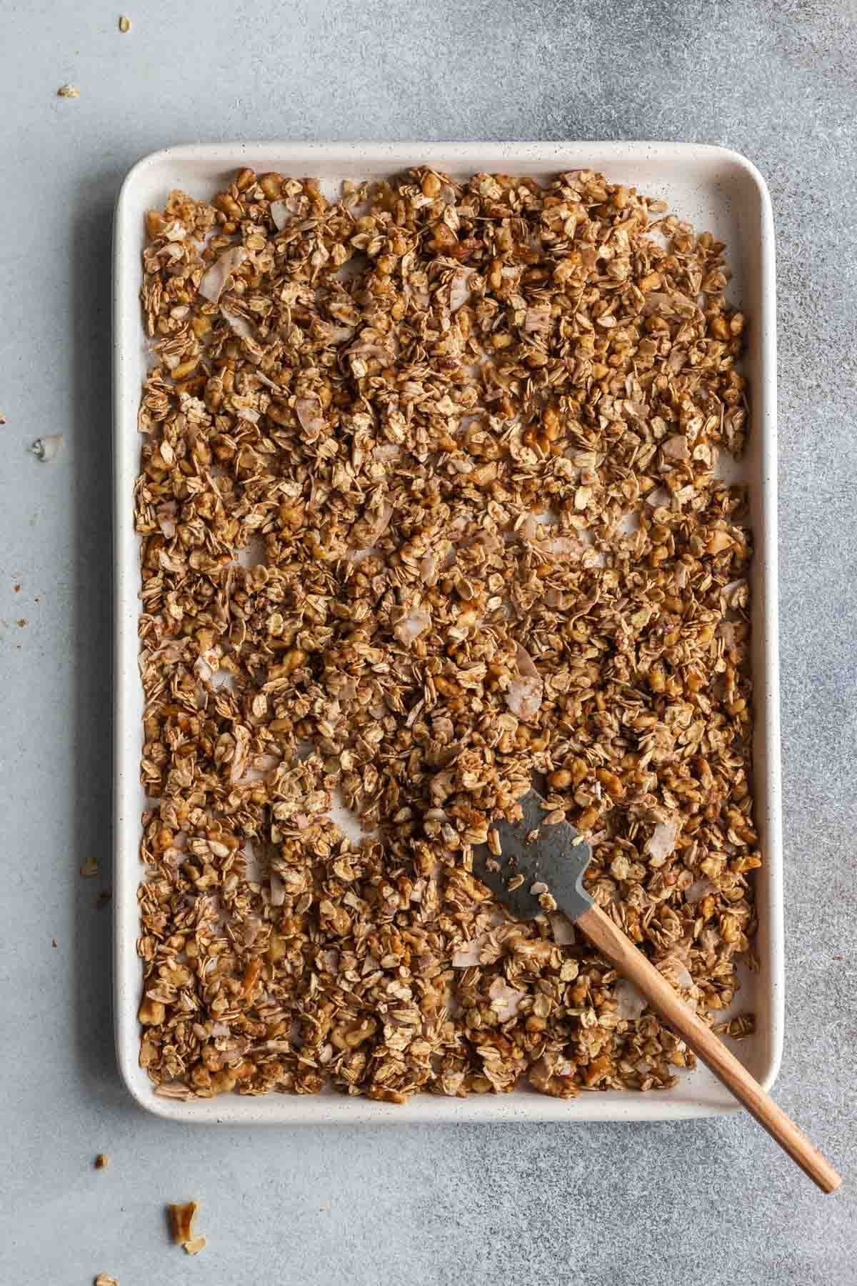 Maple walnut granola spread out on a baking sheet and ready for the oven.