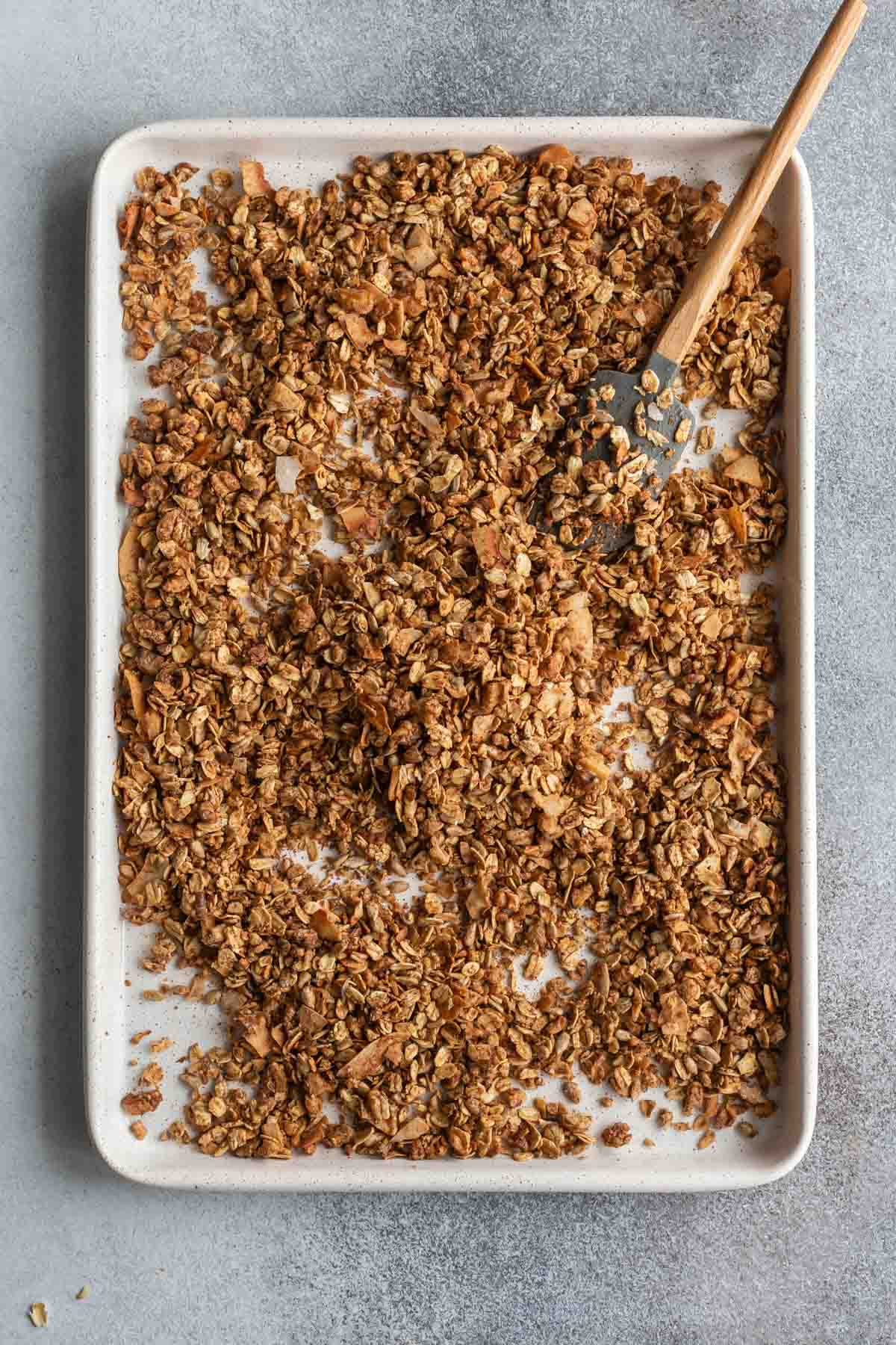 Maple granola baked up golden brown on a baking sheet.