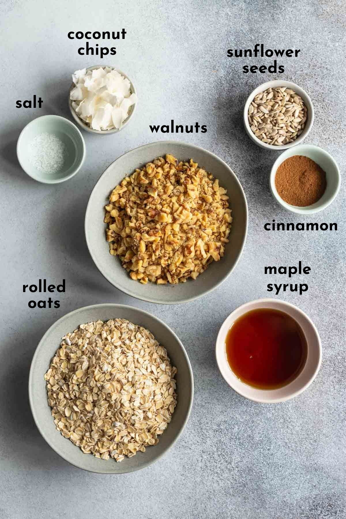 Ingredients to make this maple granola recipe arranged individually and labelled.