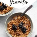 Pinterest image of maple granola in a grey bowl and topped with blackberries.
