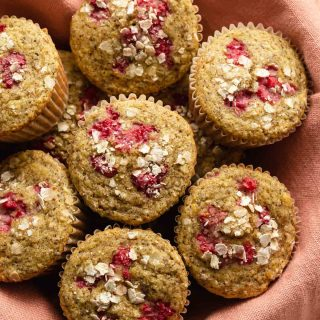 Up close view of raspberry lemon muffins in a basket lined with a pink cloth.