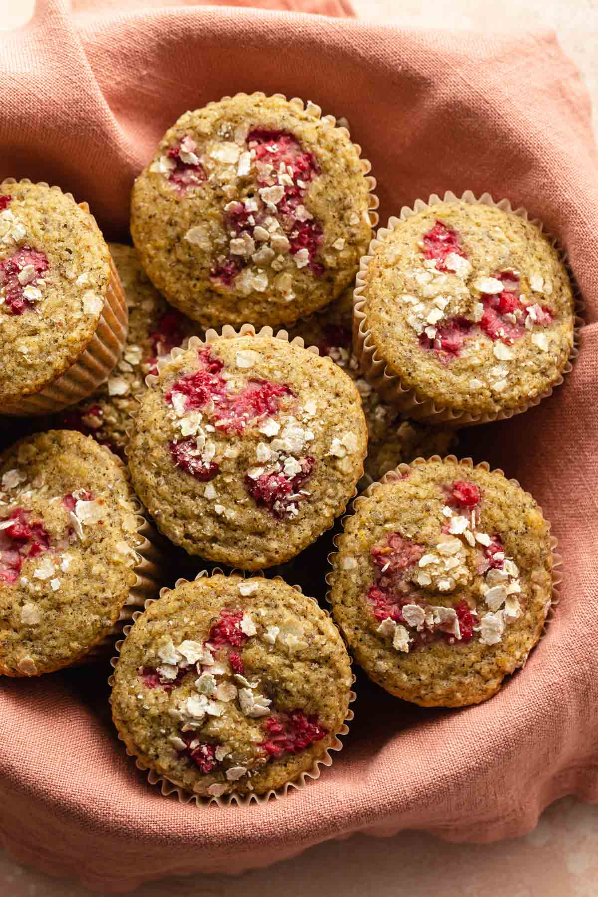 Overhead view of raspberry muffins in a basket lined with a pink napkin.