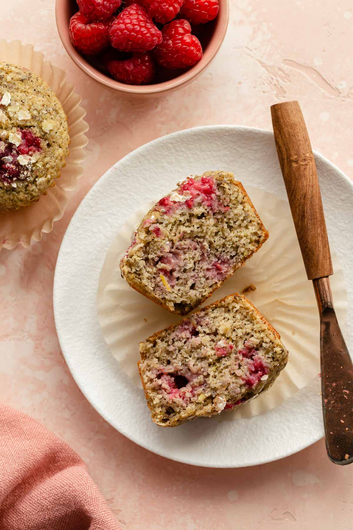 Overhead view of a raspberry lemon muffin cut in half and exposing the tender crumb texture.