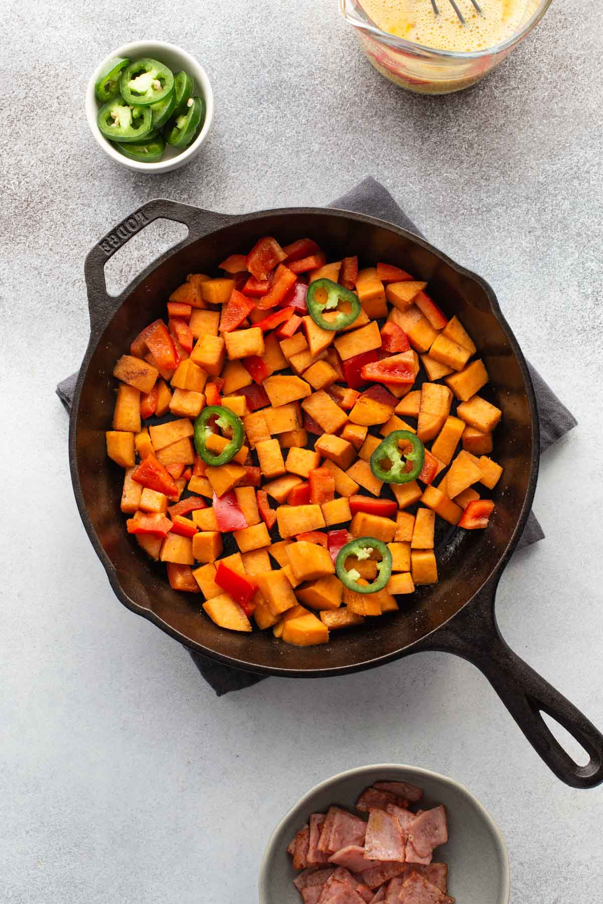 Sweet potatoes and peppers chopped and arranged in a cast iron skillet.