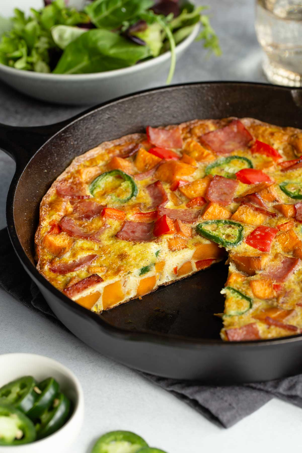 Close up side view of the frittata in a skillet with a slice removed.