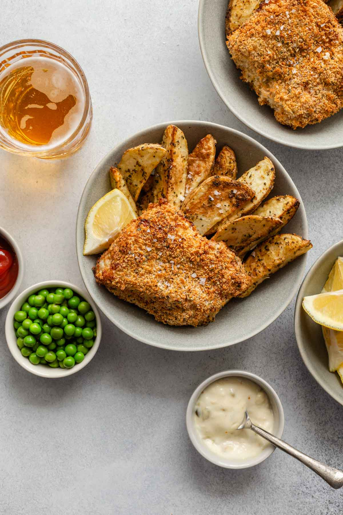 Overhead view of two bowls of breaded fish and wedge fries with peas and tartar sauce off to the sides.