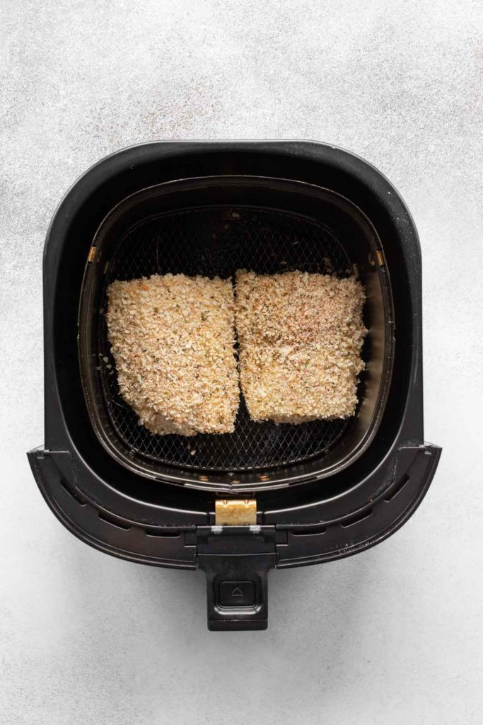 Overhead view of two uncooked breaded cod fillets in an air fryer basket.