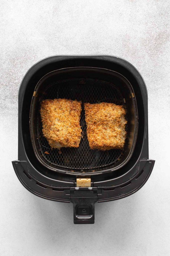 Overhead view of two air fried cod fillets in an air fryer basket.