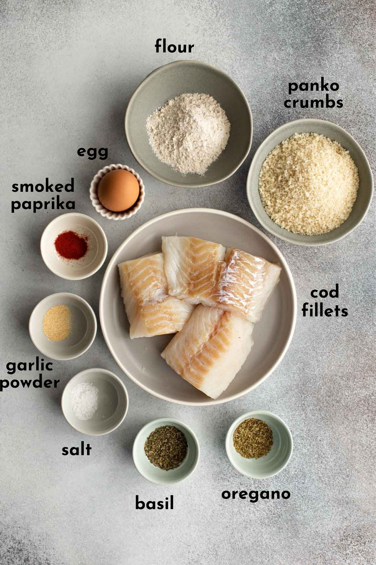 Overhead view of ingredients to make air fried cod arranged individually and labelled.