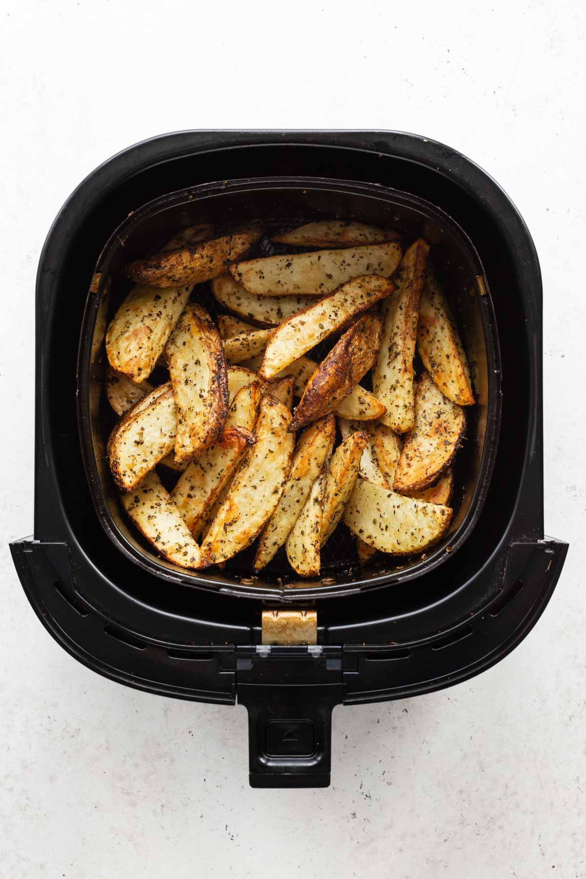 Overhead view of air fried potato wedges in an air fryer basket.