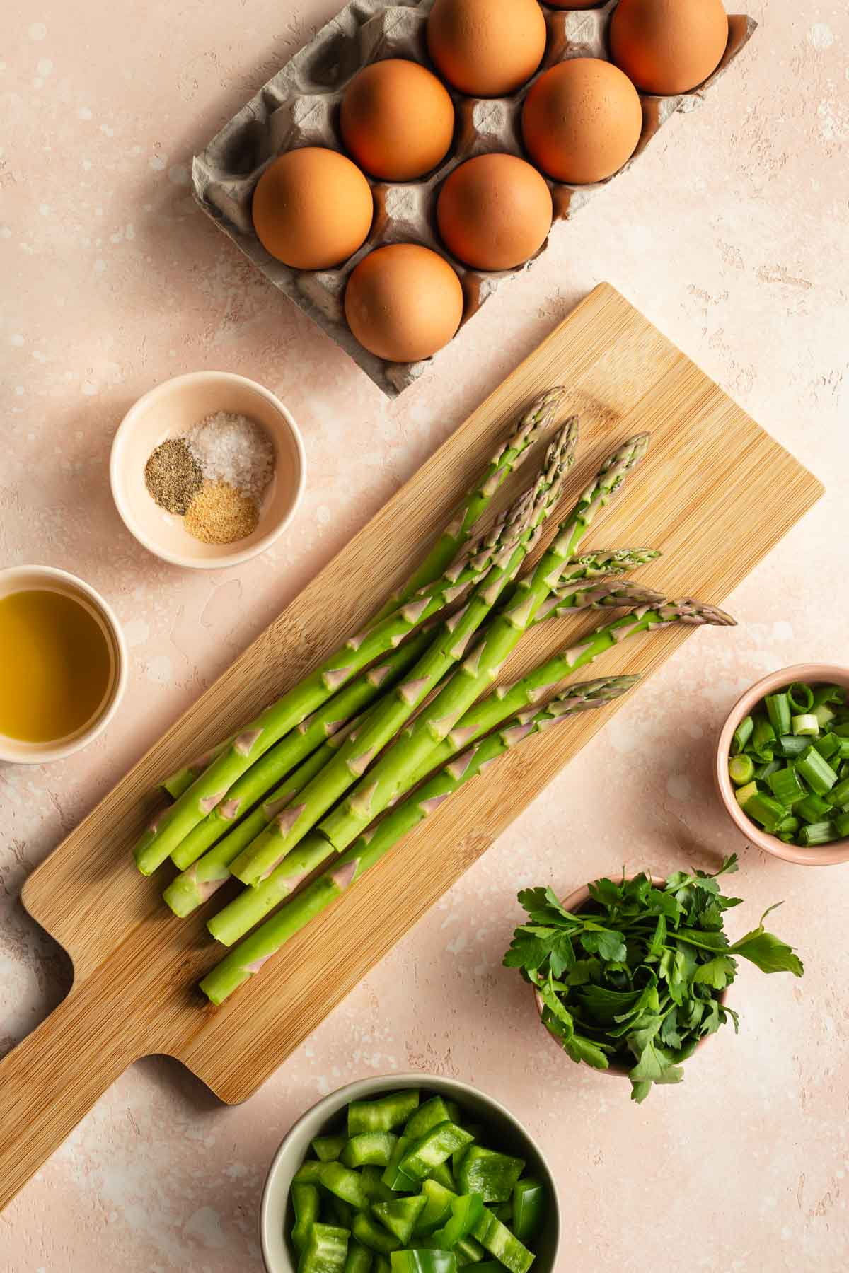 Overhead view of asparagus on a cutting board surrounded by other quiche ingredients.