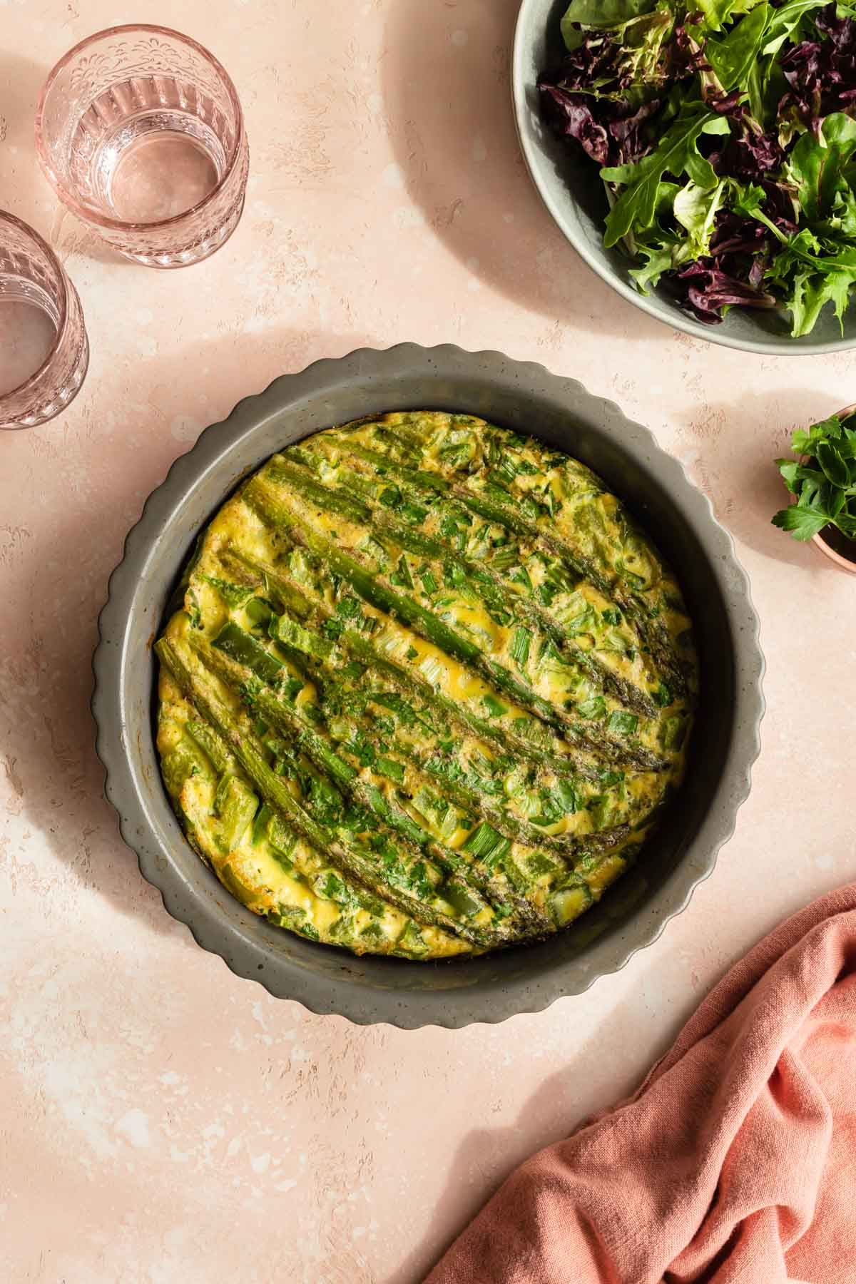 Overhead view of an asparagus quiche in a grey pie plate on a pink surface.