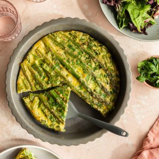 Overhead view of a crustless asparagus quiche with slices removed and a salad off to the side.