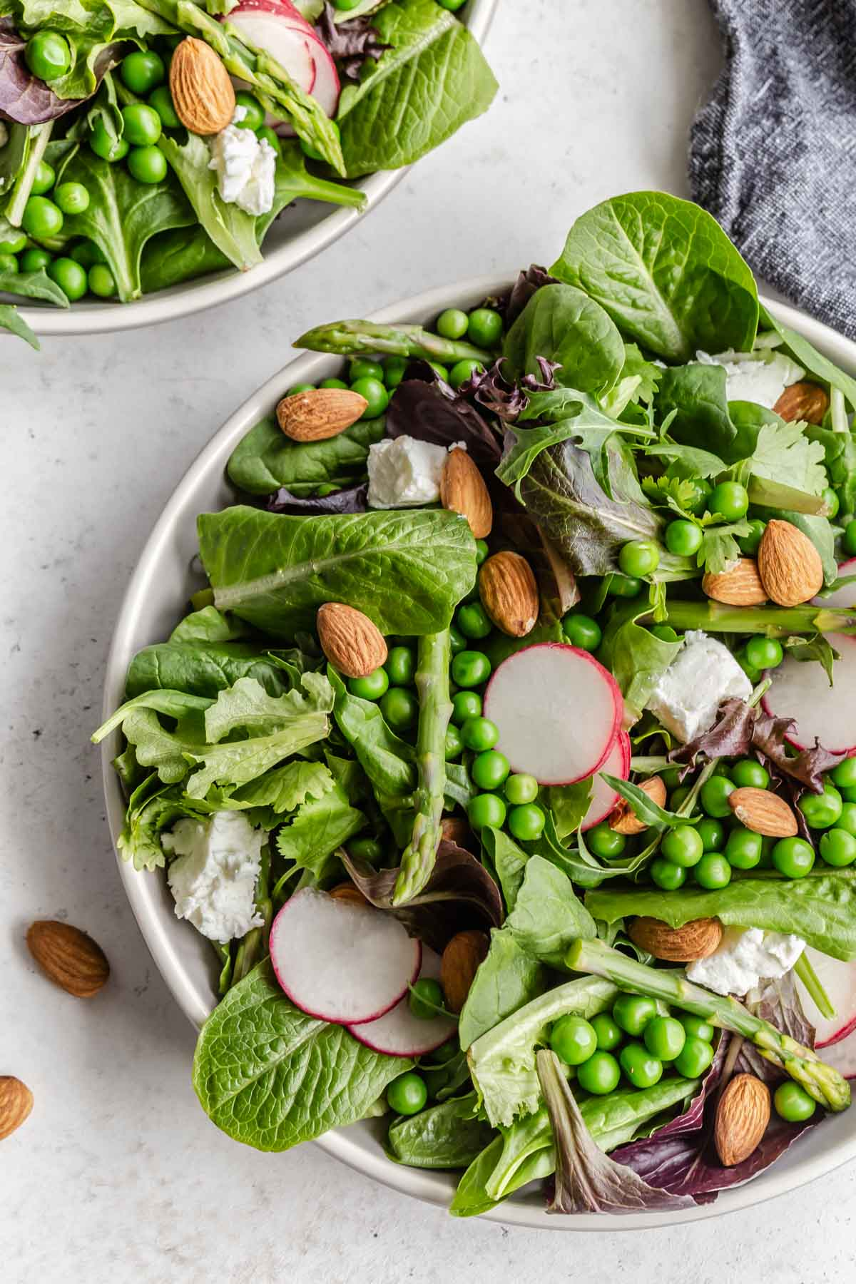 Up close overhead view of an asparagus and pea salad on a plate.