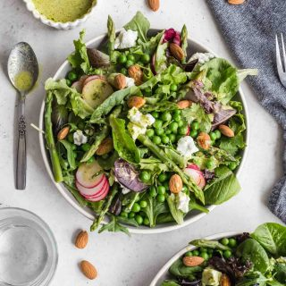 Overhead view of a spring salad on a plate with another salad and vinaigrette off to the sides.