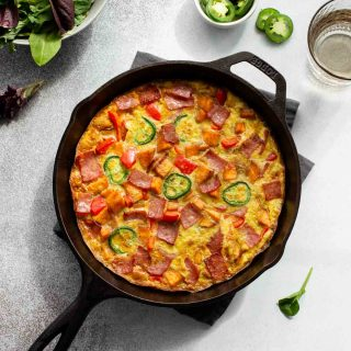 Sweet Potato Frittata with turkey bacon in a cast iron skillet.