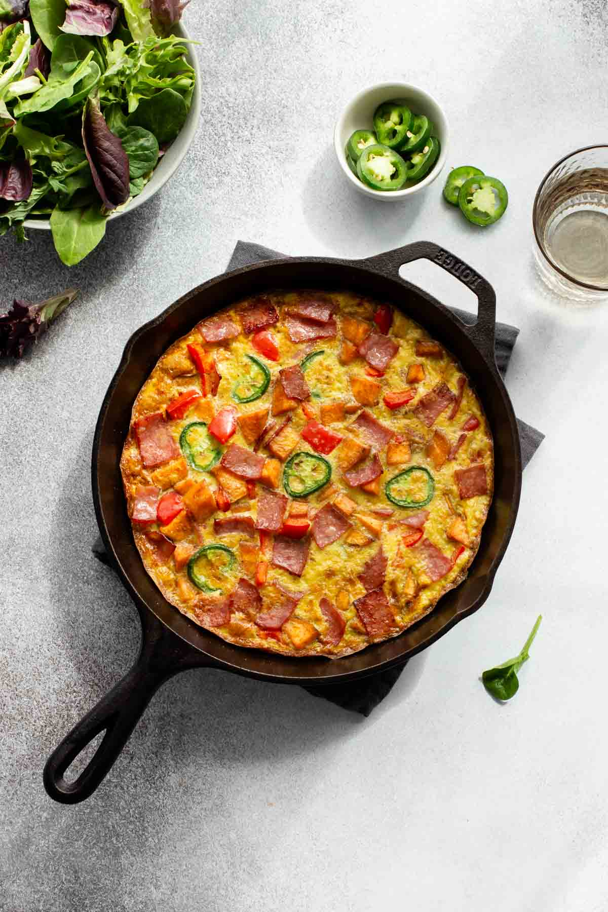 Overhead view of a sweet potato frittata in a cast iron skillet with a green salad off to the side.