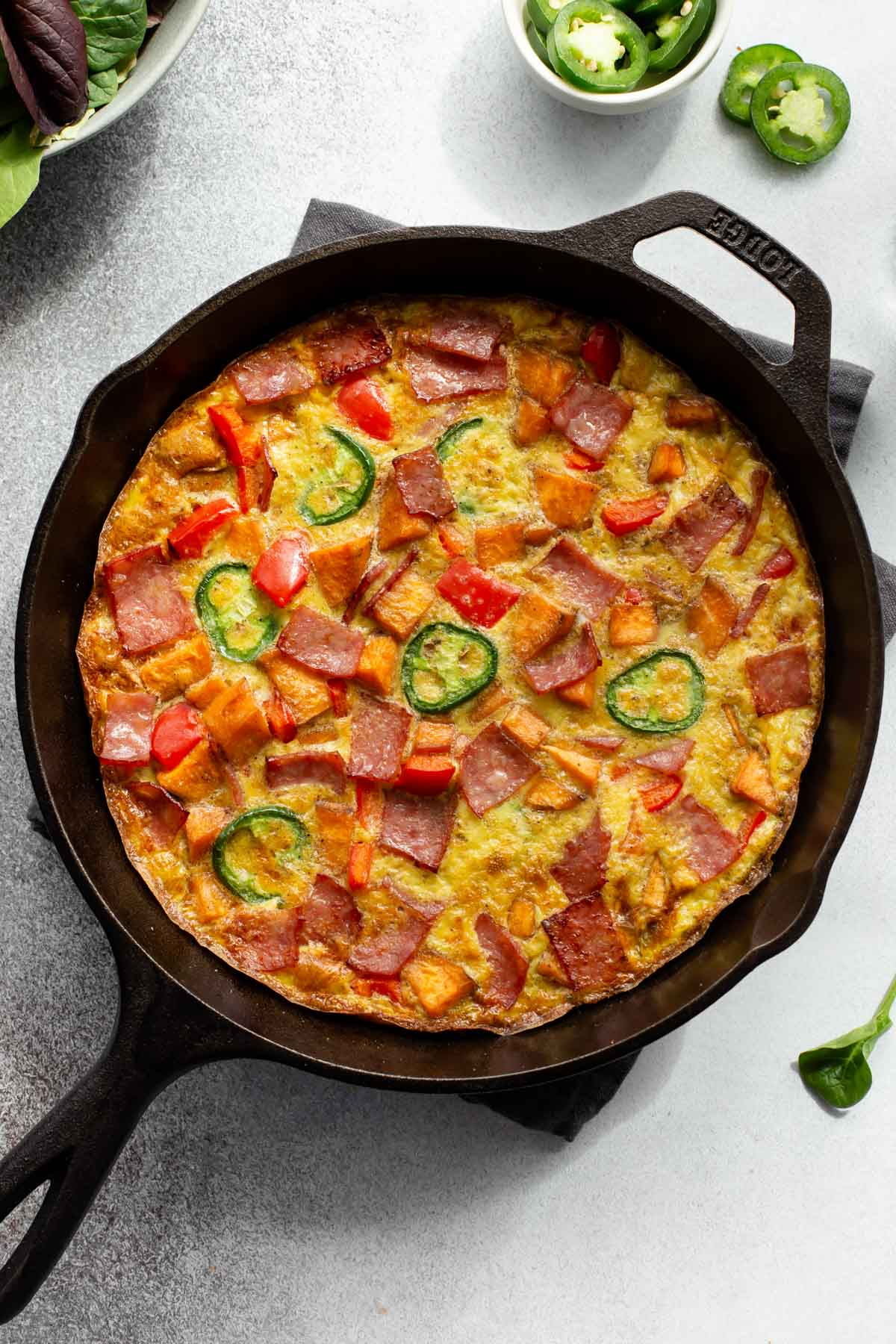 Up close overhead view of a frittata with sweet potato in a cast iron skillet.