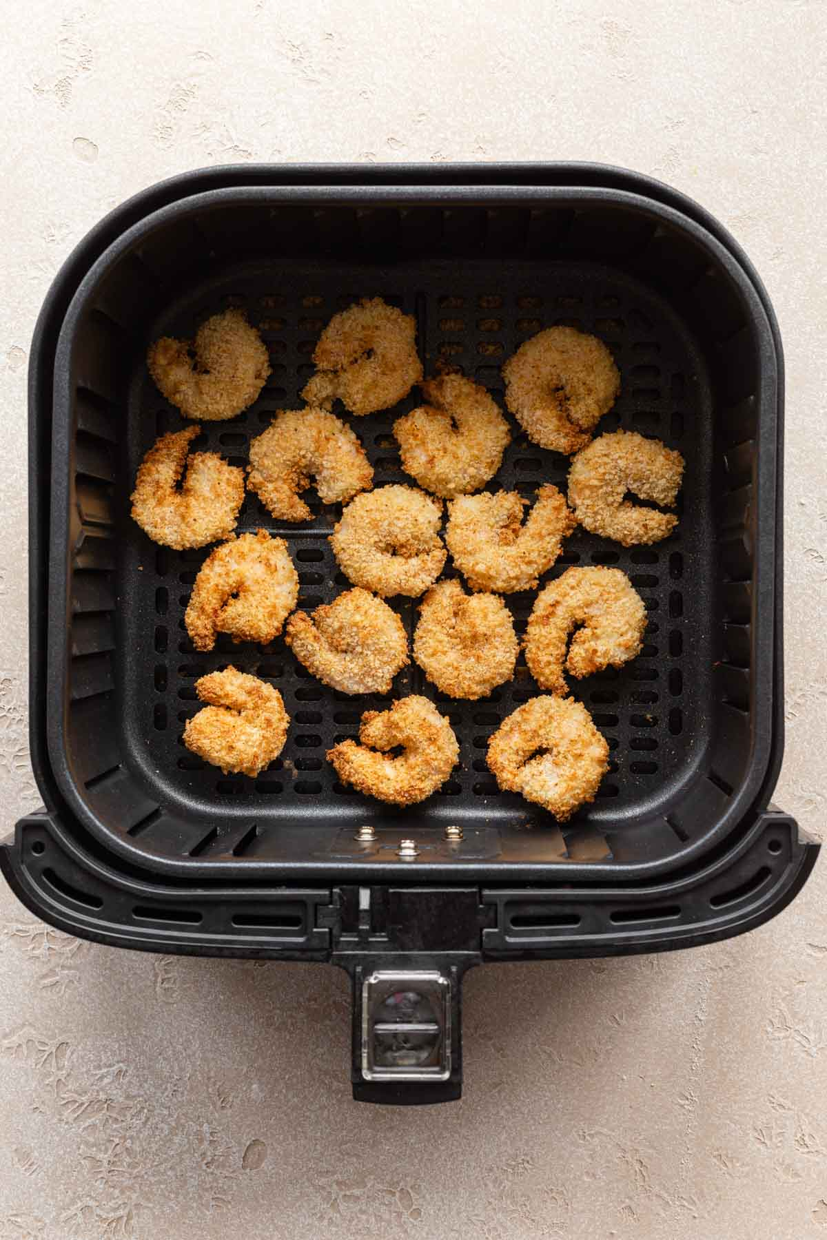 Overhead view of air fried breaded shrimp in an air fryer basket.