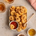 Overhead view of air fryer breaded shrimp on a plate with seafood sauce and a wooden honey dipper.