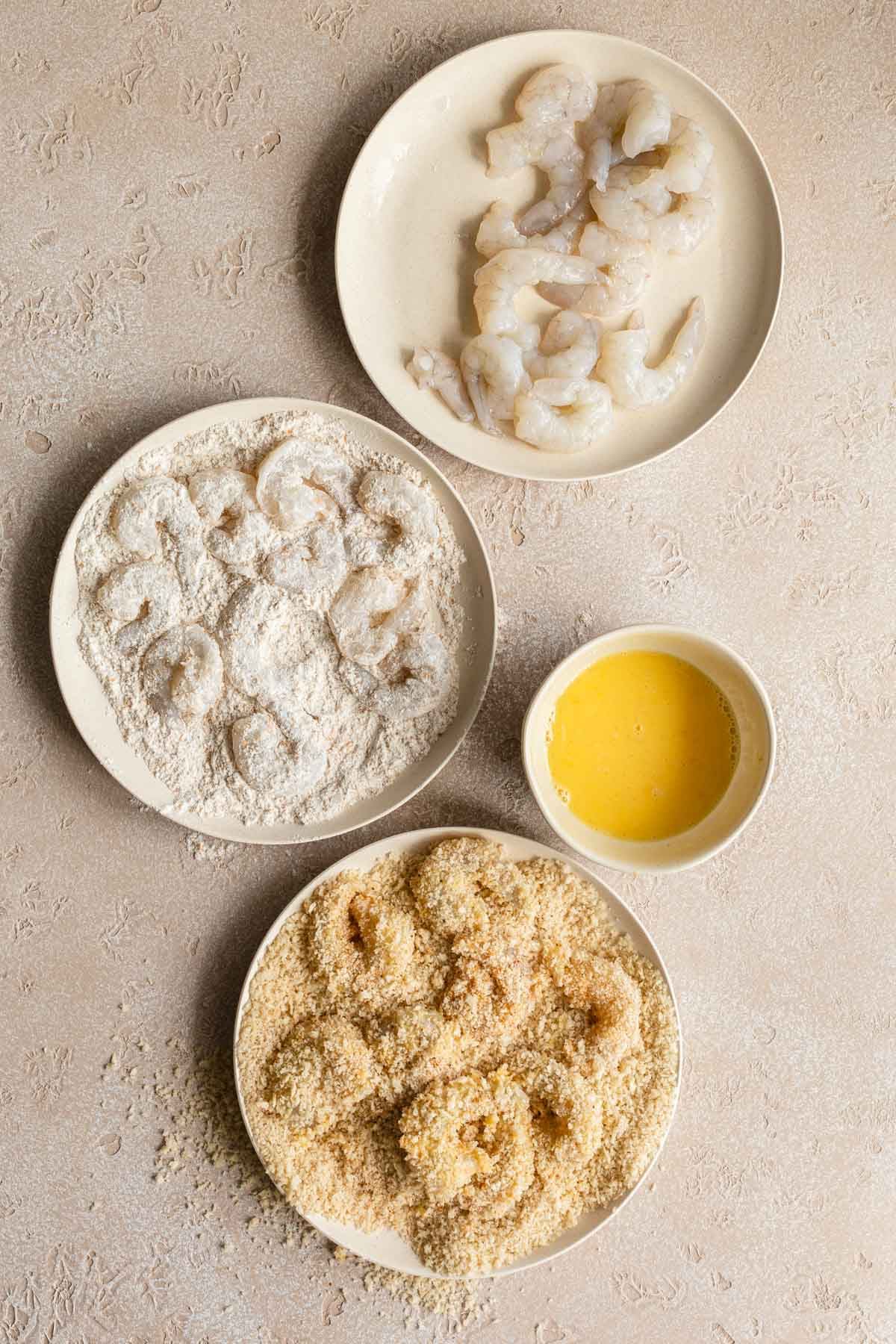 The process of breading the shrimp by coating in flour, egg and panko crumbs.