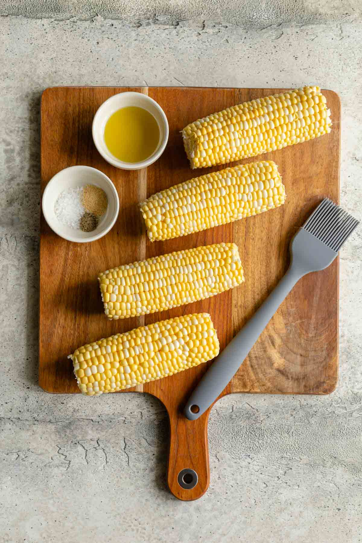 Ingredients to make air fryer corn on the cob arranged on a wooden cutting board.