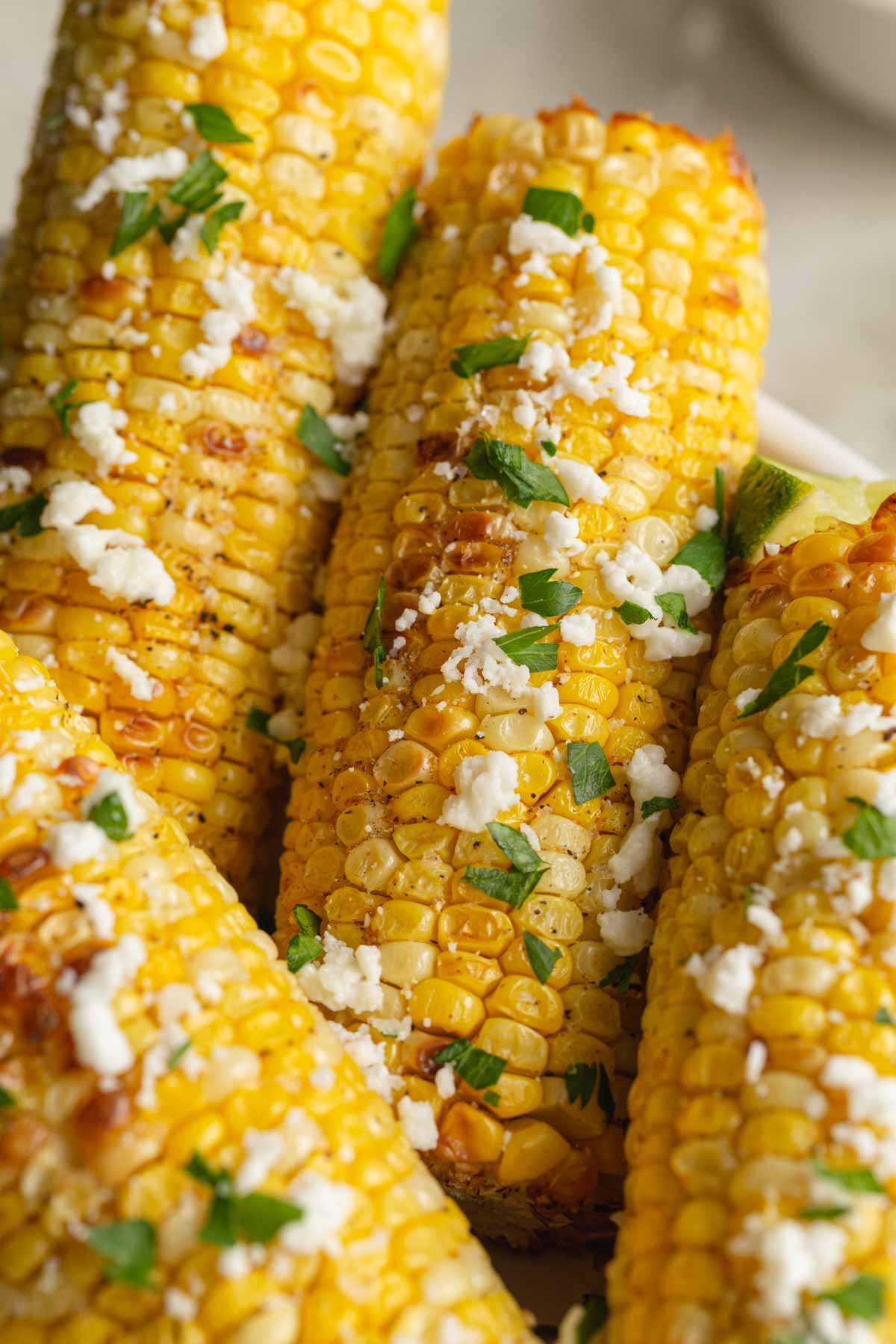 Close up of air fried corn on the cob topped with crumbled feta and chopped parsley.